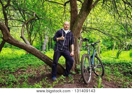 Young man cyclist shows thumb up in beautiful forest lifestyle outdoors summertime journey concept