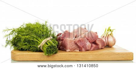Cutting board with raw pork diced dill and garlic isolated on white background.