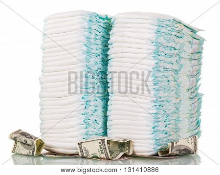 Stacks of children's diapers and money isolated on white background.