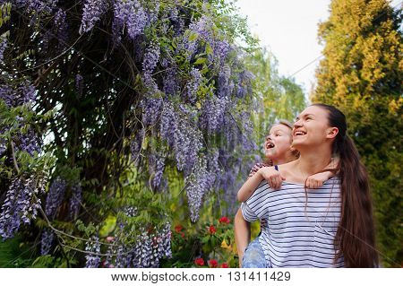 Young woman with daughter in park. They are enthusiastically looking at the blooming wisteria. The faces of the enthusiastic smiles. They were good together. Best of the rest is walk in the fresh air