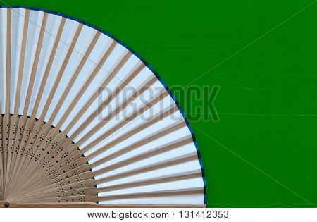 Typical Japanese hand fan made on the wooden green table