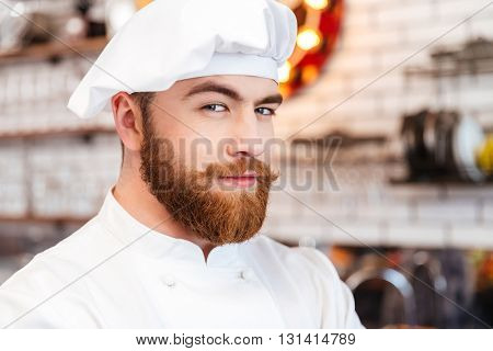 Closeup of handsome smiling bearded chef cook in white hat and uniform on the kitchen