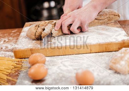 Closeup of hands of man baker cutting bread on wooden board on the kitchen