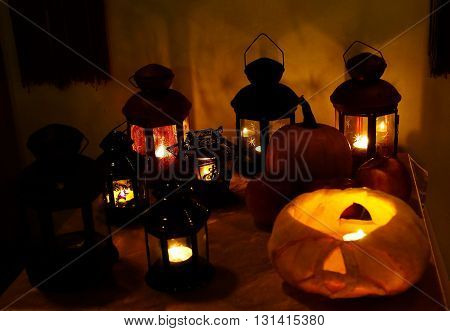 candles in sconces and pumpkin stand on a table in the dark