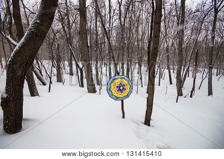 photo of handmade Native American mandala in the winter snowy forest