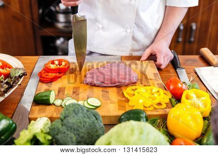 Closeup of cheif cook coooking meat and salad with fresh vegetables on the table