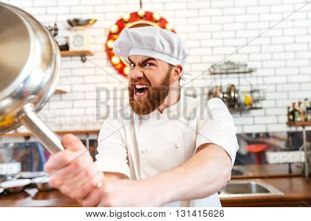 Crazy mad chef cook threatening with frying pan on the kitchen