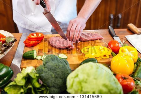 Hands of chef cook cutting and preparing meat with fresh vegetables on the table