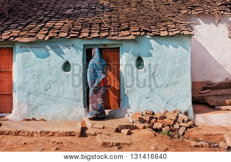 Blue rural house and woman in traditional sari opens the door of family home in Madhya Pradesh, India