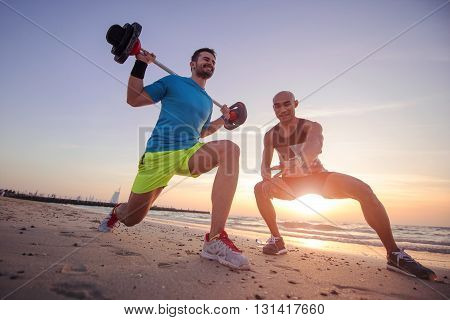 Man training hard with the help of personal trainer.
