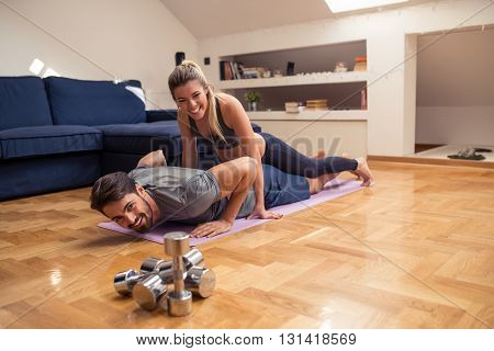 Couple training together at home in a living room.
