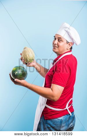 handsome indian male chef holding water melon and musk melon, asian male chef holding fruits, isolated over blue background