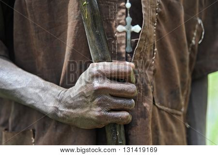 Christian African farmer hands holding a cane