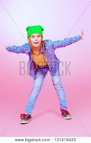 Pretty modern little girl with braids over pink background. Kid's style.