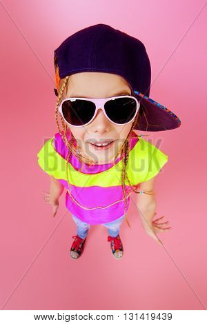 Trendy little girl in a cap smiling to camera. Kid's fashion. Happy childhood.