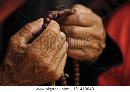 Old hands woman holding a tibetan buddhist necklace