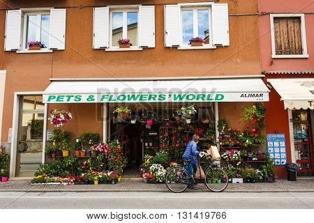 Garda Italy - May 03 2016: Buyer with a bicycle near the flower boutique