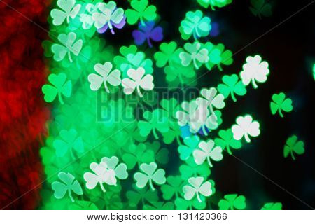 Blurring lights bokeh background of green clovers. Happy Saint Patrick's Day Background