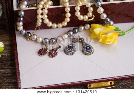 Jewellery in treasure box with yellow fresia flowers