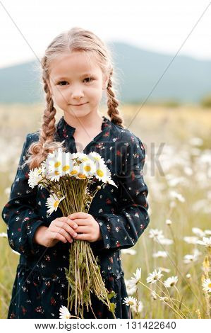 Smiling baby girl 4-5 year old holding chamomiles in meadow outdoors. Looking at camera. Childhood.