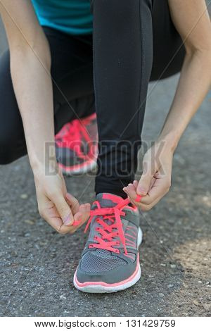Woman binding her shoes before jogging in nature.