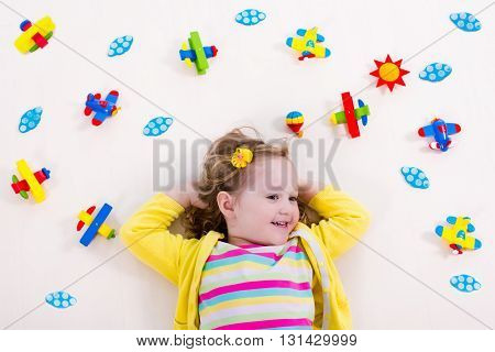 Child playing with wooden airplanes. Preschooler kid flying around the world. Kids travelling and playing. Children at day care or kindergarten. View from above.