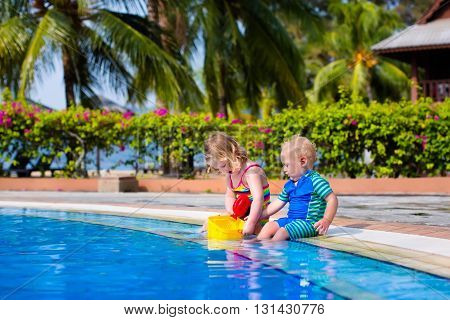 Girl and boy playing in swimming pool in tropical resort. Child learning to swim. Toddler kid with toy bucket and watering can. Summer beach vacation for family with children. Water fun for kids.