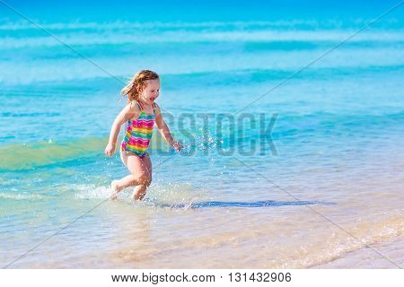 Happy child running and jumping in the waves during summer vacation on exotic tropical beach. Holiday on ocean coast for family with young children. Kids play at the sea. Little girl learning to swim.