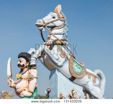 Chettinad India - October 16 2013: Combination of Ayyanar and his horse against blue skies. Ayyanar is the village protector here the Kadiapatti village.