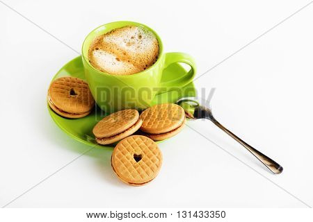Coffee with foam in a green cup saucer spoon and tasty cookies.