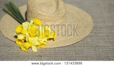 Springtime - bouquet of Easter daffodil flowers and a straw hat lying on a wooden table
