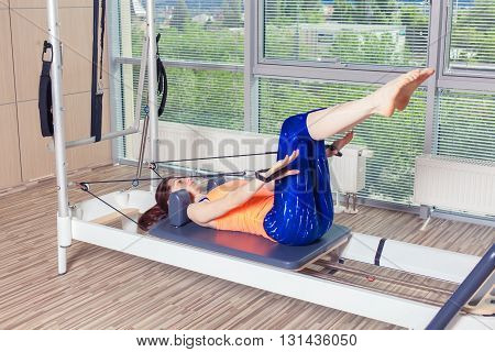 Pilates reformer workout exercises woman brunette at gym indoor.