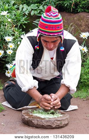 TAQUILE PERU - MARCH 20 2015:Man in traditional clothes makes shampoo at Taquile Island at lake Titicaca in Peru