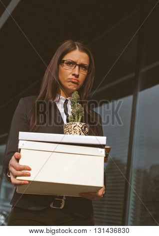 Beautiful sad looking businesswoman holding a box of her belongings after being fired