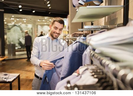 sale, shopping, fashion, style and people concept - happy young man in shirt choosing jacket in mall or clothing store