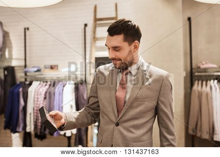 sale, shopping, fashion, style and people concept - elegant young man or businessman in suit choosing bow-tie in mall or clothing store