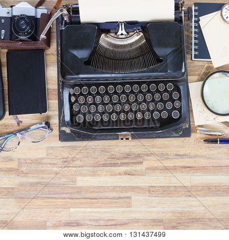 black vintage typewriter and supplies on desktop with copy space, top view