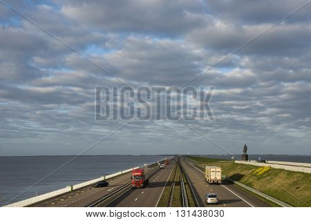 Afsluitdijk The Netherlands - April 19 2016: Afsluitdijk between Friesland and Noord-Holland at the IJsselmeer with highway monument and cars.