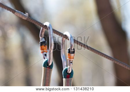 the carbines fastened to a cable in rope park