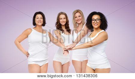 gesture, friendship, beauty, body positive and people concept - group of happy different women in white underwear holding hands together on top over violet background