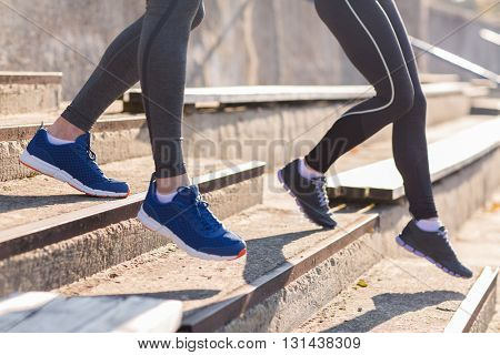 fitness, sport, exercising and lifestyle concept - close up of couple or friends running downstairs on stadium