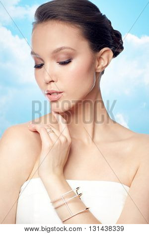 beauty, jewelry, wedding accessories, people and luxury concept - beautiful asian woman or bride with golden ring and bracelet over blue sky and clouds background