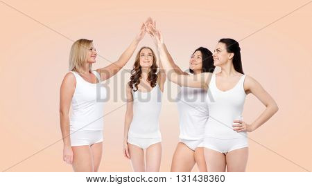 gesture, friendship, beauty, body positive and people concept - group of happy different women in white underwear making high five over beige background