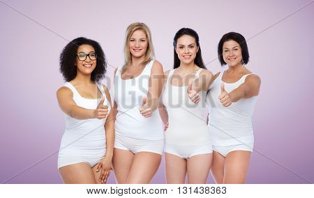 gesture, friendship, beauty, body positive and people concept - group of happy different women in white underwear showing thumbs up over violet background