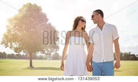 love, relations, holidays, dating and people concept - happy couple wearing sunglasses walking over summer park background