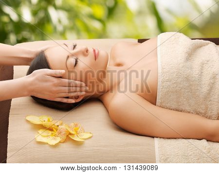 spa and holidays - woman in spa getting facial massage