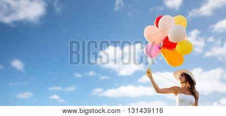happiness, summer, holidays and people concept - smiling young woman wearing sunglasses with balloons over blue sky background