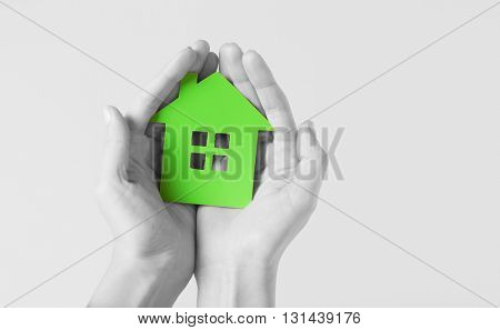 real estate and family home concept - closeup picture of female hands holding green blank paper house