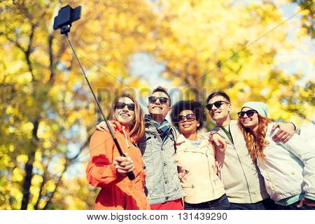 tourism, travel, people, season and technology concept - group of smiling teenage friends taking selfie with smartphone and monopod over autumn park background