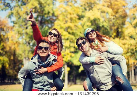 friendship, leisure, season and people concept - group of happy teenage friends in sunglasses having fun over autumn park background
